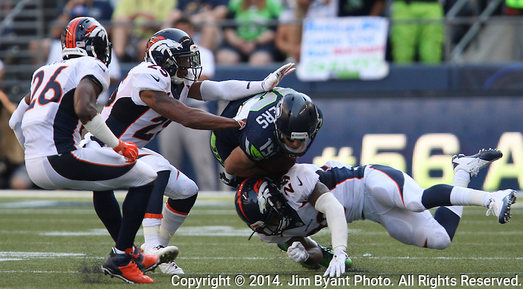 Seattle Seahawks  wide receiver Bryan Walters (19) is tackled Denver Broncos cornerback Bradley Roby (29), Chris Harris Jr., and Rahim Moore (26) after catching a pass for an 11-yard gain in the fourth quarter at CenturyLink Field in Seattle, Washington on September 21, 2014. The Seahawks won 26-20 in overtime    ©2014. Jim Bryant Photo. All rights Reserved.