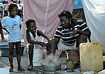 A survivor of the devastating January 12 earthquake cooks a meal outside her makeshift tent in a camp for homeless families in Port-au-Prince, Haiti.