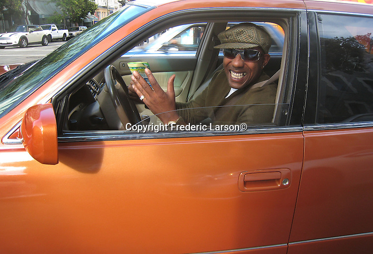 A cheerful driver smiles at a intersection to the people walking in the crosswalk of the North Beach district of San Francisco, California.