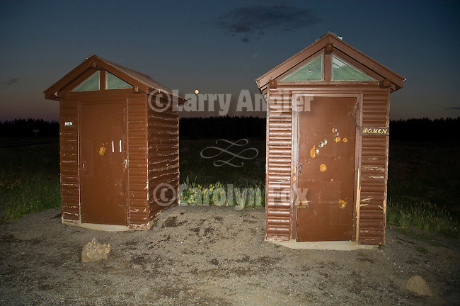 Twin brown outhouses, with rising moon atop Grand Mesa in the Colorado Rockys