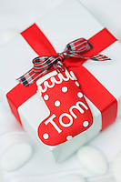A label in the shape of a Christmas stocking made of Fimo personalises this present