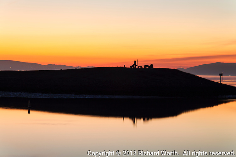 A par course exercise station stands in silhoutte against an orange sunset, reflected in San Francisco Bay.