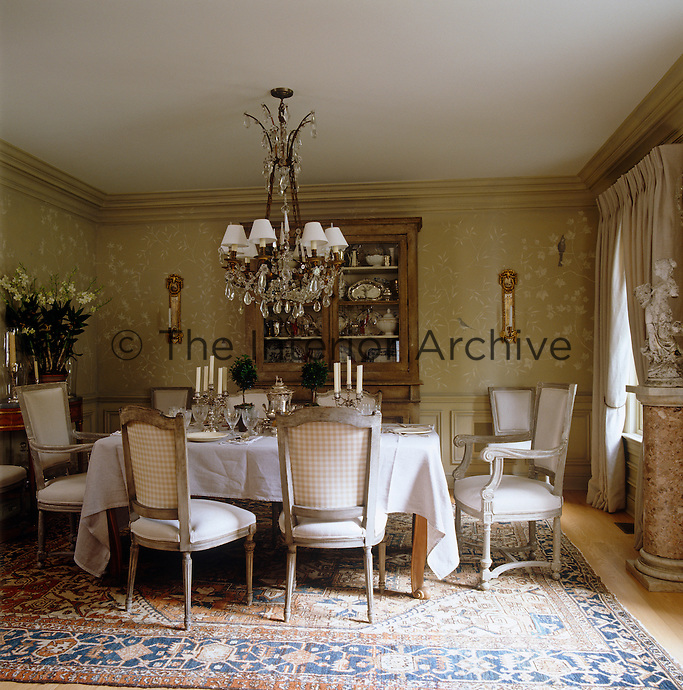 The walls in this dining room have been hand painted in a white botanical Chinoiserie pattern whilst the ceiling is dominated by a 19th century French bronze and crystal chandelier