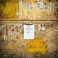 A notice taped to a wall, covered in grafitti and the remnants of posters, in a residential neighbourhood that reads: 'Please Keep Clean and Quiet'.