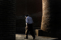 Old man walking in the streets of Ichan-Kala, Khiva, Uzbekistan, seen from behind and against the light on July 7, 2010, in the afternoon.