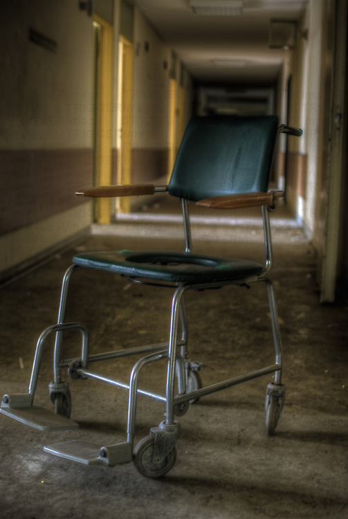 An old abandoned hospital in the former East Germany with a solitary chair in a hospital corridor