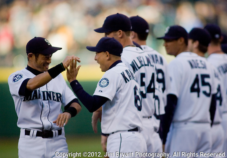 Seattle Mariners Ichiro Suzuki (R) and Munenori Kawasaki, of Japan, high five one another during pre game introductions before their game against the Oakland Athletics at SAFECO Field in Seattle April 13, 2012.  © 2012. Jim Bryant Photo. All Rights Reserved.