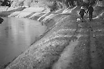 Two people walking along a canal bank on a winters day