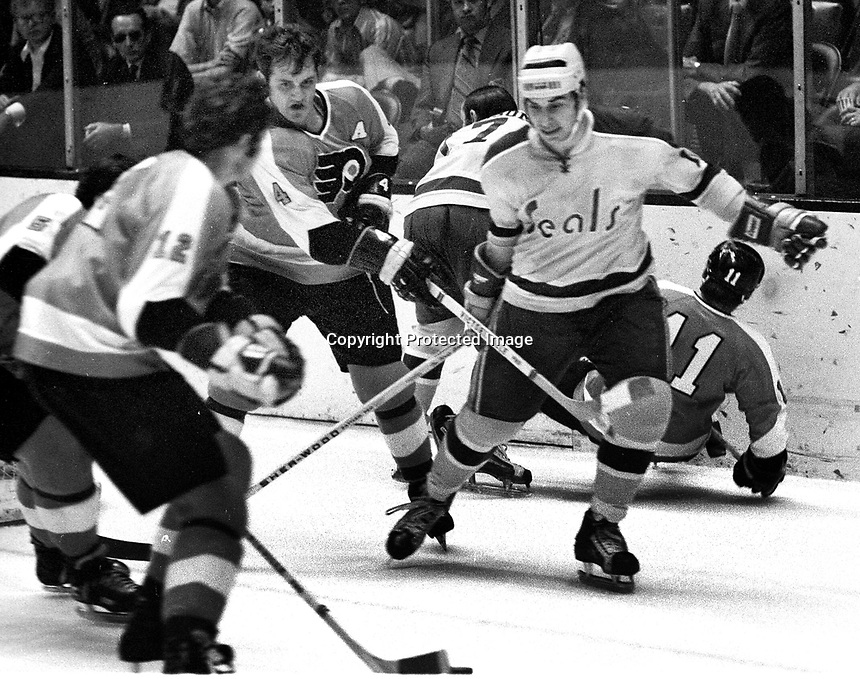 Seals vs Flyers action, Gary Croteau, battles Flyers Gary Domhoefer, and Barry Ashbee. (1971 photo/Ron Riesterer)