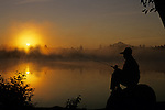 Woman silhouetted at sunrise along shoreline fishing sitting on a rock Lake Cassidy Snohomish County Washington State USA