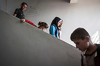 In this Thursday, Sep. 26, 2013 photo, Syrian children walk downstairs as they attend the public school in Madaya village as classes started in the Idlib province countryside of Syria. Children have come back to school in the rebel controlled territory despite the constant threaten of shelling and the ongoing fighting, and public schools still operating financially under the Syrian government administration. (AP Photo)