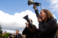 Bullhorns, fighting words and a cameraman. Amanda Schemkes (right) leads a chant during a protest on the University of Washington campus. Hundreds turned out to protest the construction of a new $125 million underground animal research lab on campus at the University of Washington in Seattle, Wash. on April 25, 2015. (© Karen Ducey Photography)