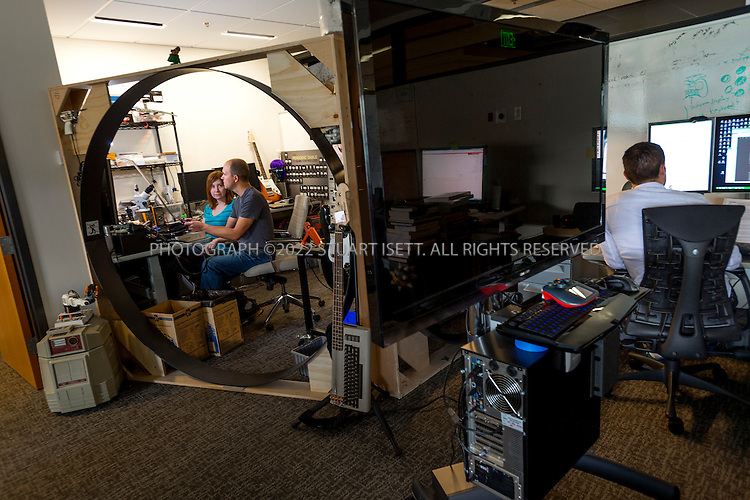 6/18/2012--Bellevue, WA, USA..Valve Software's offices in Bellevue, WASH., just east of Seattle. The office is set up as a 'boss less' office that is fluid and non-hierarchical. Desks come with wheels so that they can be easily moved and reconfigured to create new work spaces for new projects. The desks can also be raised or lowered for comfort or to create a standing work space...Here, Valve employees working in the company's hardware lab, including Jeri Ellsworth (left) and Jeff Bellinghausen (2nd left). Ellsworth used a large circular wooden frame from a display board to create an entrance to their space....Stuart Isett for The Wall Street Journal