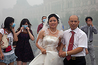 Moscow, Russia, 07/08/2010. .A wedding party in Red Square try to protect themsleves from the worst smog so far in the record high temperatures of the continuing heatwave. Peat and forest fires in the countryside surrounding Moscow have resulted in the Russian capital being blanketed in heavy smog.