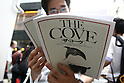 July 3, 2010 - Tokyo, Japan - A man read a pamphlet of the Oscar-winning dolphin hunting documentary 'The Cove' near cinema running the movie in Tokyo, Japan, on July 3, 2010. Despite pressure from groups who say the film is anti-Japanese, 'The Cove' will be shown at six theaters in Tokyo and five other Japanese cities beginning Saturday, followed by Nagoya Cinematheque and 15 other theaters across Japan from Aug. 14.