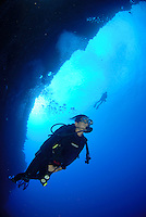 silhouette of two divers at the back wall Molokini Maui Hawaii.