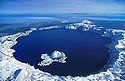 Wizard Island and Crater Lake in winter snow; Crater Lake National Park, Oregon.