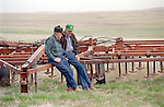 Veteran farmers talk on machinery for sale during a farm auction in eastern Colorado
