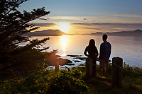 A man and woman watch the sunset from a scenic overlook in Fort Ambercrombie State park, Kodiak Island, Alaska.