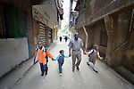 Abdel Karim, a refugee from the Darfur region of Sudan, walks his children to school in the morning through the streets of Cairo, Egypt. Karim and his wife have both taken adult education classes provided by St. Andrew's Refugee Services, which is supported by Church World Service. His children, from left, are Ziad, 9; Ahmed, 4; and Dana, 7.