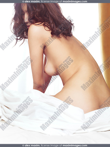 Beautiful nude asian woman sitting naked on a bed in bright sunlight