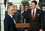 King Hussein of Jordan addresses a White Houase gathering on December 20, 1982 as President Reagan listens. Reagan's Special Envoy to the Middle East Philip Habib (glasses) is in teh center.