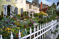 A white wrought iron picket fence encloses an entry garden.