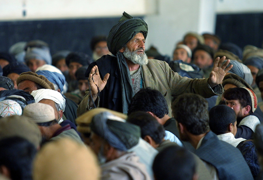An Afghan man addresses a meeting in the town of Mahmood Raqi, to select representatives for the Loya Jirga April 25, 2002. The Loya Jirga, or Grand Tribal Council, is Afghanistan's traditional legal instrument, and will meet in Kabul in June to select Afghanistan's leadership for 18 months. No women attended the meeting.