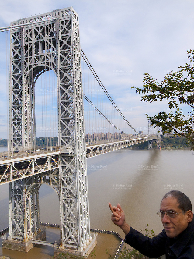"USA. New Jersey state. Fort Lee. Joseph Rodriguez making a rude hand gesture. View on The George Washington Bridge. The George Washington Bridge is a suspension bridge spanning the Hudson River, connecting the Washington Heights neighborhood in the borough of Manhattan in New York City to Fort Lee, Bergen County, New Jersey. Interstate 95 and U.S. Route 1/9 cross the river via the bridge. U.S. Route 46, which is entirely in New Jersey, ends halfway across the bridge at the state border. The bridge has an upper level with four lanes in each direction and a lower level with three lanes in each direction, for a total of 14 lanes of travel. A path on each side of the bridge's upper level carries pedestrian and bicycle traffic. As of 2007, the George Washington Bridge has the greatest vehicular capacity of any bridge in the world, carrying approximately 106 million vehicles per year, making it the world's busiest motor vehicle bridge. In Western culture, the finger (as in giving someone the finger or the bird), also known as the middle finger, is an obscene hand gesture, often meaning the phrases ""fuck off"" (""screw off""), ""fuck you"" (""screw you"") or ""up yours"". It is performed by showing the back of a closed hand that has only the middle finger extended upwards..23.10.2011 © 2011 Didier Ruef"