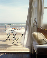 The beach at Camber Sands provides an idyllic backdrop for tea, laid on a vintage table on the deck of a restored 1930s beach house