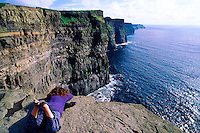 Woman peering over cliff, Cliffs of Moher, County Clare, Ireland