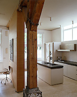 The kitchen in this converted 19th century depot was designed by John Pawson and is dominated by a massive timber beam a legacy of the building's original structure