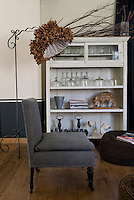 In this corner of the living room a floor lamp with a quirkily poetic shade made of dried leaves has been placed next to an antique chair re-covered in contemporary grey flannel