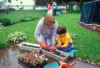 Learning to plant flowers, grandma and grandson intergenerational -gardening in the backyard, family time teaching young child by older adult person