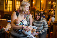A mother standing and breastfeeding her 12 week old baby in the family restaurant and play area in a pub.<br /> Lancashire, England, UK<br /> <br /> Date Taken:<br /> 07-01-2015<br /> <br /> &copy; Paul Carter / wdiip.co.uk