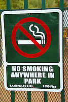 No Smoking anywhere in Park, Sign, Green, White Letters, International Smoking Symbol,