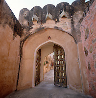The imposing studded double doors of the gateway to the fort which open onto a cobbled driveway through the gardens