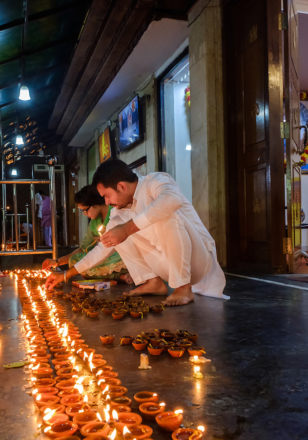 NEW DELHI, INDIA - CIRCA OCTOBER 2016: Couple lighting candles for the Diwali celebration at the Sai Baba Temple in the Hauz Khas area of New Delhi. Diwali is also known as festival of lights, for the Hinduism, it spiritually signifies the victory of light over darkness, good over evil, knowledge over ignorance, and hope over despair. Its celebration includes millions of lights shining on housetops, outside doors and windows, around temples and other buildings in the communities.