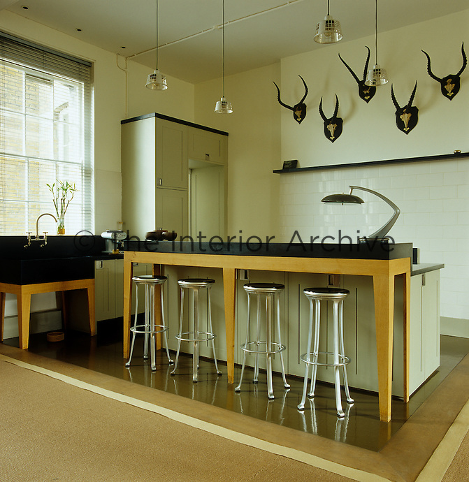 The central island in the kitchen is made of oak topped with a black Corian work surface to match the unusual and elegant black Belfast sink