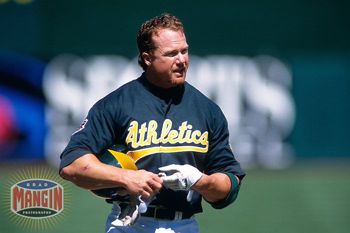 OAKLAND, CA - Mark McGwire of the Oakland Athletics takes off his batting gloves during a game at the Oakland Coliseum in Oakland, California in 1997.  Photo by Brad Mangin