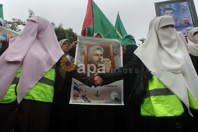 Palestinian women hold pictures of incarcerated relatives in a rally to show solidarity with prisoners held in Israeli jails, in Gaza City May 14, 2012. One in three of the 4,800 Palestinians serving time in Israeli jails began refusing food on April 17 in protest against their detention without trial and to demand better conditions, like an increase in family visits and the ending solitary confinement. Photo by Ashraf Amra