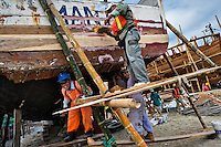 Ecuadorian workers caulk a traditional wooden fishing vessel, inserting hemp fiber between planks of the ship's shell, in an artisanal shipyard on the beach in Manta, Ecuador, 14 September 2012. The construction process takes 3-4 months to complete, depending on the ship size and purpose (fish capture methods). Although a wooden boat tends to be more stable on the sea and less expensive to build (up to $0.5 million USD), it needs a maintenance every 2 years, while a fiberglass-made boat, costing almost double the wooden one, may serve 5-6 years without any repairs. The shipyard produces 6-8 vessels every year.
