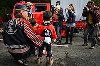 """Fire department chief with children having his photo taken. Housui Gassen (fire-hose battle), Bizen city, Okayama pref, Japan, February 2, 2014. The annual Bizen """"Housui Gassen"""" (fire-hose battle) takes place in the Hinase port area. Opposing teams of fire-fighters spray each other with hoses before the event culminates with a display of coloured water from the hoses."""
