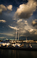 Moored boats at the San Leandro Marina under a sky filled with ominous clouds a few minutes before sunset on a winter evening.