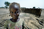 A girl stands in front of the wall of a burned hut in Leu, a village in the contested Abyei region along the border between Sudan and South Sudan. The village was looted and burned in 2011 when soldiers and militias from the northern Republic of Sudan swept through the area, chasing out more than 100,000 Dinka Ngok residents. A few thousand families have returned to the region since northern combatants withdrew in 2012, yet their life is precarious. In Leu, the Catholic Church rehabilitated a clinic and drilled a well. For political and logistical reasons, the Catholic Church is one of the few organizations willing to openly accompany the people of Abyei during these uncertain times.