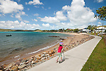 A girl rides her scooter along the Victoria Parade esplanade.  Thursday Island, Torres Strait Islands, Queensland, Australia