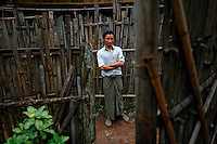 """Wailin Aung, 24 year old ethnic Karen refugee is seen through the gate of a home at the Mae La refugee camp near Mae Sot June 3, 2012. Asked about Aung San Suu Kyi's visit to the camp Wailin Aung said """"I don't understand politics but I don't want to go back to Myanmar. Never."""" Myanmar's pro-democracy leader Aung San Suu Kyi visited on Saturday Mae La, the biggest refugee camp along the Thailand-Myanmar border where tens of thousands of her compatriots found shelter after escaping from Myanmar.  REUTERS/Damir Sagolj (THAILAND)"""