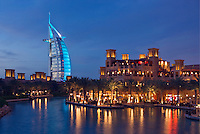 Burj al Arab Hotel, an icon of Dubai built in the shape of the sail of a dhow, stands on an artificial island just off Jumeirah Beach. View across Madinat Jumeirah.  Evening. Dubai. United Arab Emirates.