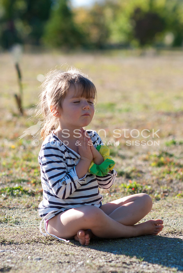 Young girl sitting cross-legged and meditating / praying on the ground in summer, New Zealand - stock photo, canvas, fine art print