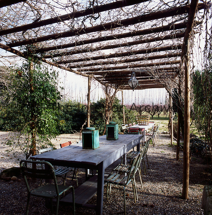 Tables and chairs are set out on a gravelled area shaded by a wooden pergola, allowing a view of the garden.